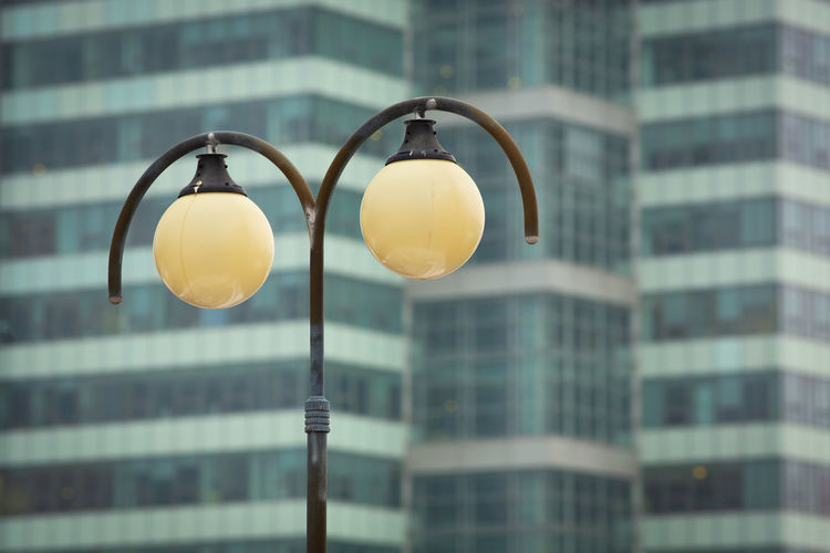 Old fashioned street lamp with office building in the background Building Exterior Built Structure Lighting Equipment Architecture City Focus On Foreground Low Angle View Building No People Day Yellow Glass - Material Outdoors Close-up Street Window Modern Street Light Transparent Hanging Electric Lamp