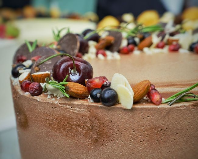 Close-up of fruit and nut decoration on top of chocolate cake.