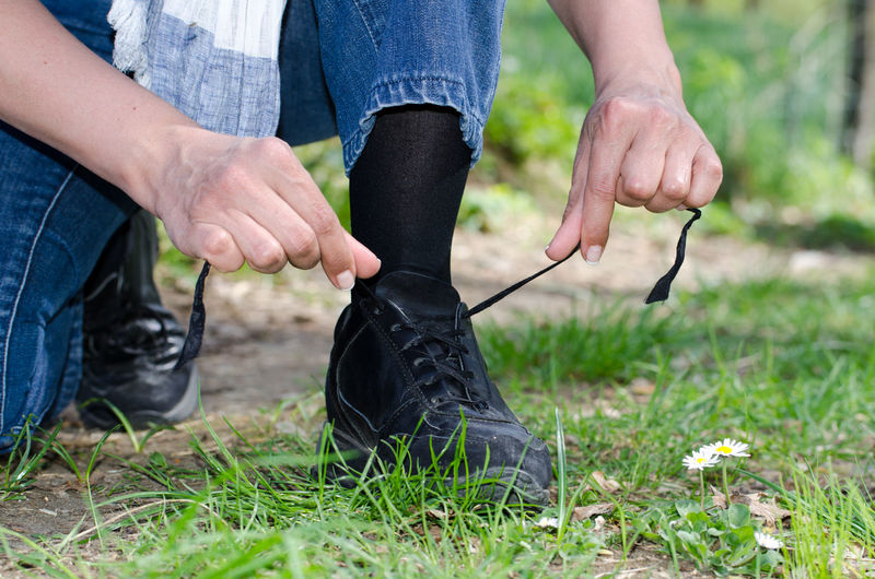 Low section of woman tying shoelaces on grass
