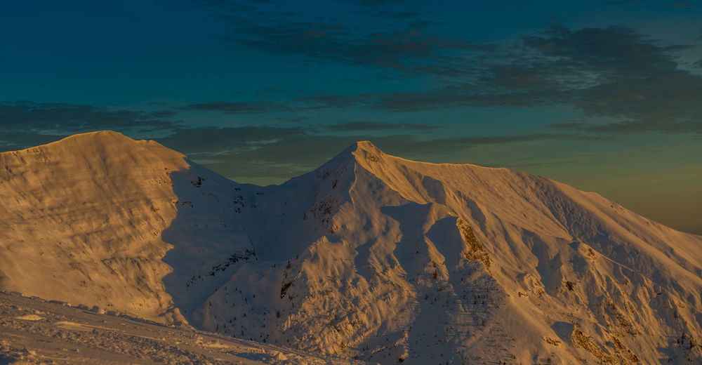 Snow-covered mountain grem at sunset