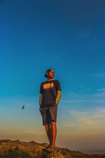 Man standing against blue sky during sunset