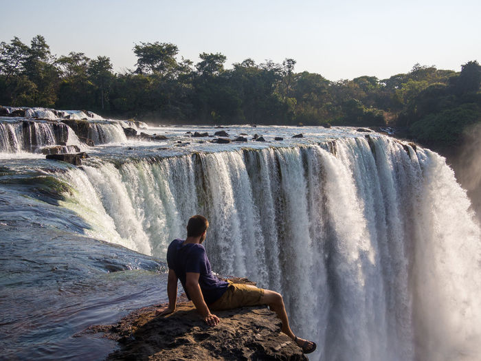 Young man sitting on edge of lumangwe waterfall, zambia
