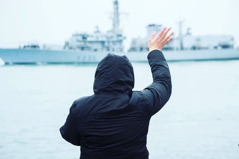 Rear view of person waving at ship