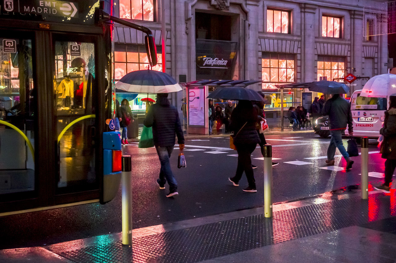 city, architecture, building exterior, street, illuminated, group of people, night, city life, built structure, walking, transportation, wet, real people, motion, road, rain, men, umbrella, women, city street, rainy season, outdoors