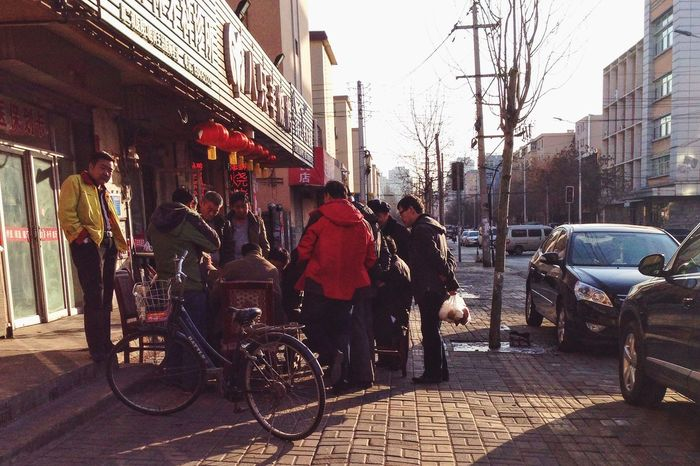 Bicycle Building Exterior Chinese Chess City City Life Incidental People Lifestyles Men Real People Recreational Pursuit Sidewalk Street Urban