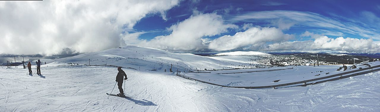 Panoramic View Of People Skiing Against Sky