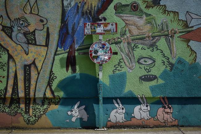 Wall art in Prenzlauer Berg including a traffic sign covered in stickers. Berlin Berlin In Summer Creativity Flowers Kollwitzplatz Multi Colored No People Outdoors Prenzlauer Berg Street Art Sun Wasserturm