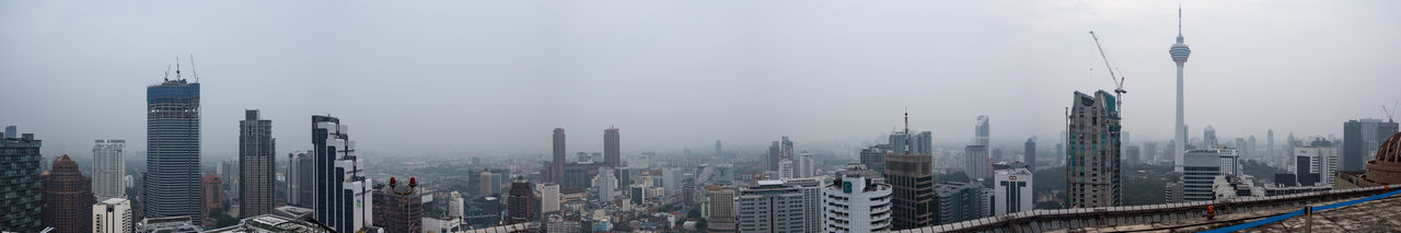 Panoramic view of urban skyline against sky