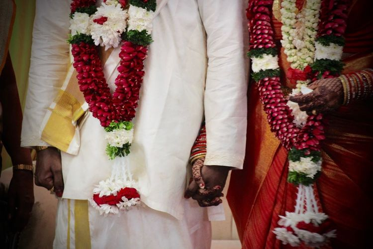 Midsection of bride and bridegroom holding hands during wedding ceremony