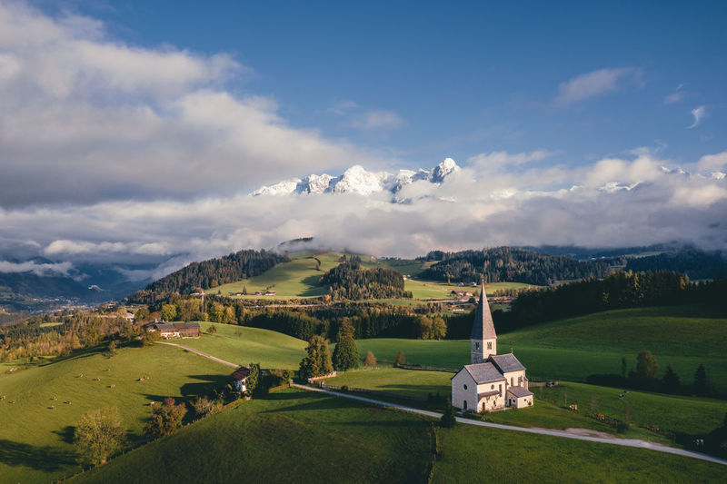 Aerial view at church on mount buchberg with snow covered mountains in the background, austria.