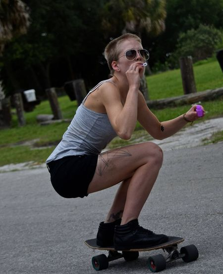 Full Length Of Woman Blowing Bubbles While Longboard Skating On Road