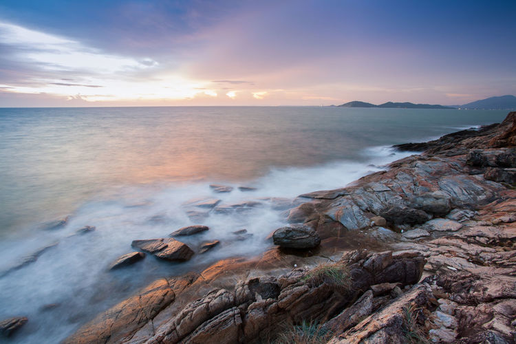 Landscape sea view at sunset timing reflection on water with foreground stone mountain by long exposure located at rayong province east of Thailand Sea Sky Rock Rock - Object Water Solid Beauty In Nature Scenics - Nature Cloud - Sky Motion Land Horizon Over Water Horizon Nature Tranquility Tranquil Scene No People Beach Outdoors