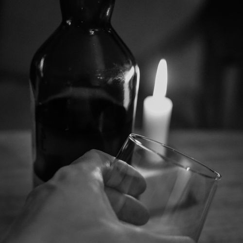 Dark night of the soul (III) Black And White Bottle Candlelight Close-up Dark Night Of The Soul Drink Flame Food And Drink Glass Hand Holding Indoors  Night Lights Selective Focus Still Life Temptation Whiskey Liquor Photographic Memory