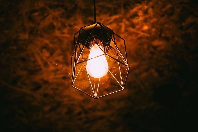 Illuminated light bulb hanging in the dark
