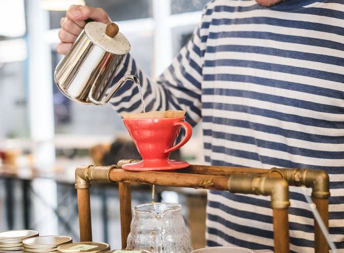 Drip Coffee Coffee Adult Barista Coffee - Drink Drip Coffee Focus On Foreground Hand Holding Human Body Part Human Hand Indoors  Kitchen Lifestyles Metal Midsection Occupation One Person Pouring Preparation  Real People Striped