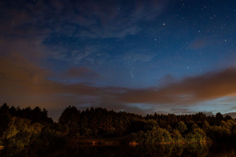 Evening landscape, a starry sky in the clouds and a comet over a forest lake.