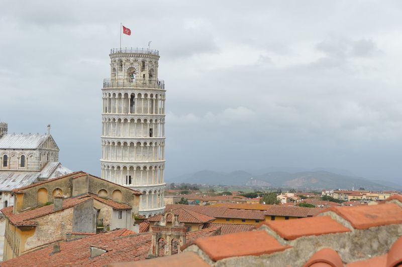 Leaning Tower Of Pisa In City Against Cloudy Sky