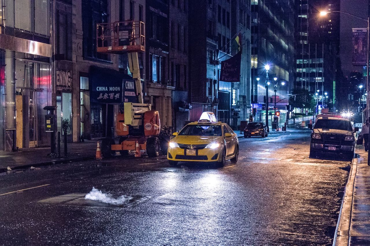 street, city, architecture, transportation, night, car, building exterior, road, illuminated, urban, yellow taxi, land vehicle, built structure, outdoors, cityscape, no people