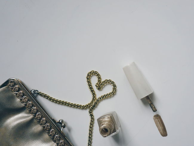 golden purse and golden nailpolish Gold Close-up No People Vintage White Backround Golden Purse Studio Shot Indoors  Nails Done Nailpolish Nail Polish Nail Beauty Fashion Luxury Gold White Background Nails White Indoors