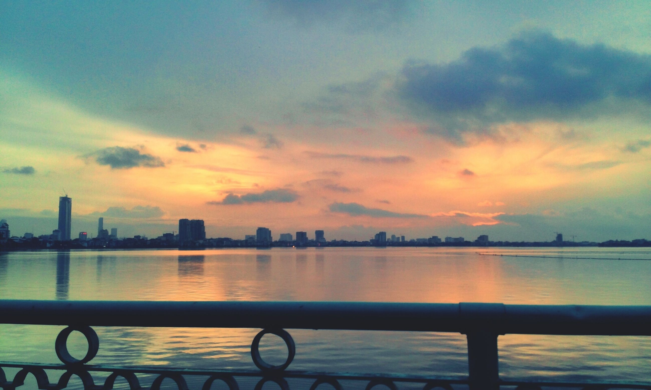 sunset, water, sky, railing, cloud - sky, sea, silhouette, river, orange color, tranquility, scenics, nature, tranquil scene, transportation, beauty in nature, built structure, cloud, bicycle, lake, outdoors