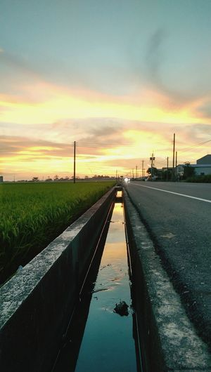 Gutter by field against cloudy sky during sunset