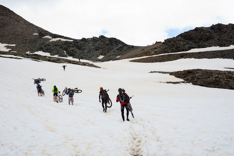 People carrying their mountain bikes on snowcapped mountain against sky