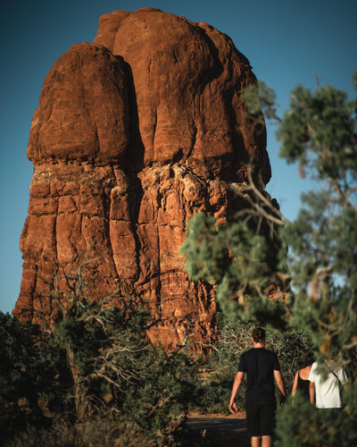 Rear view of people on rock against trees