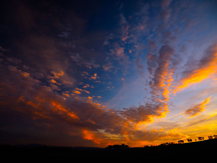 Scenic view of dramatic sky over silhouette landscape
