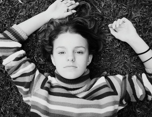 Directly Above Shot Of Teenage Girl Lying On Grassy Field