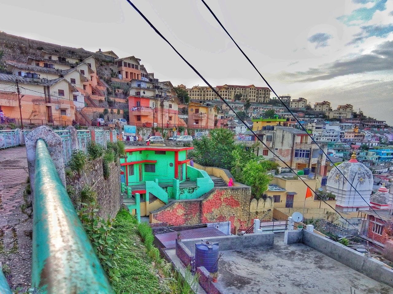 architecture, built structure, building exterior, building, residential district, sky, city, nature, no people, house, day, town, multi colored, cloud - sky, outdoors, plant, connection, community, water, wall, townscape