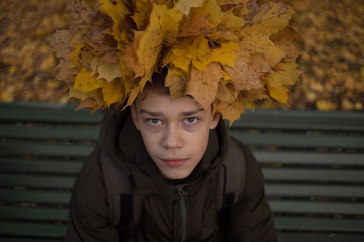 Portrait of teenage boy with yellow leaves in park during autumn