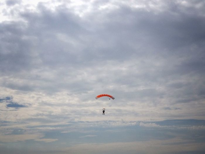 View Of Parachuting Against Cloudy Sky
