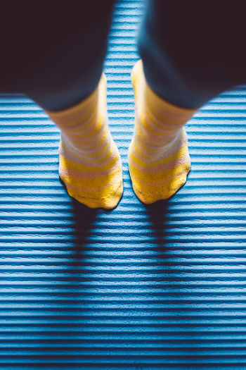 Low Section Of Person Wearing Socks Tip-Toe Standing On Floor