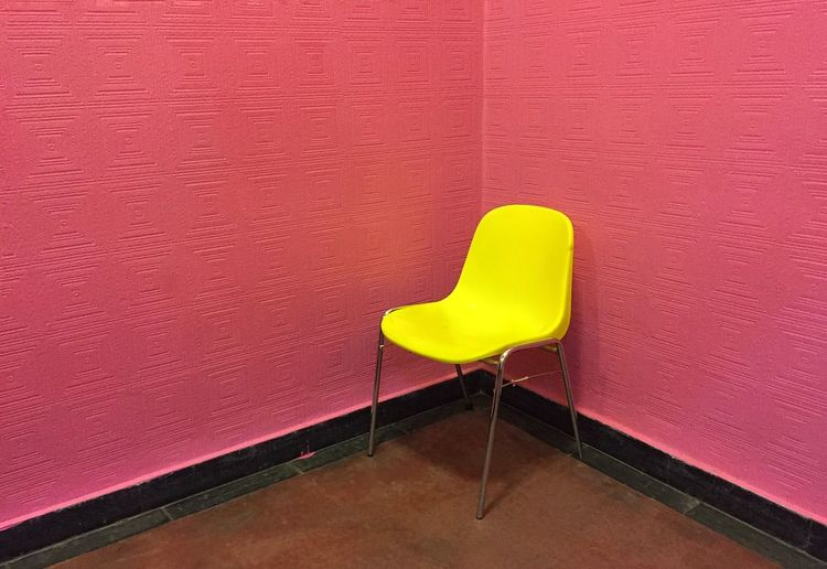 High angle view of empty yellow chair against pink wall in room