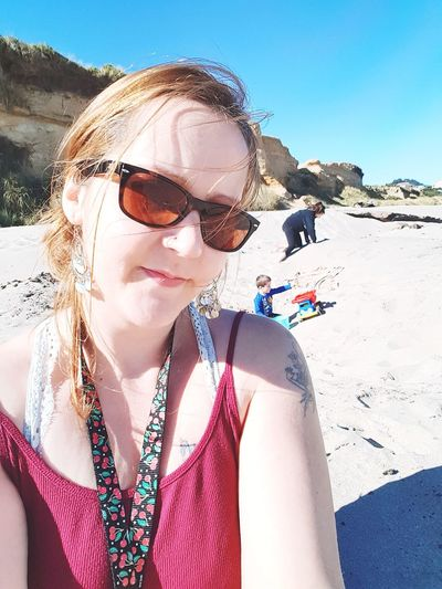 Portrait of woman wearing sunglasses at beach during sunny day