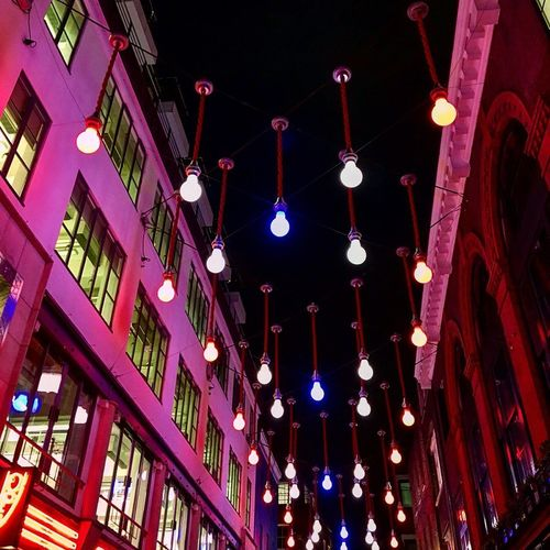Low angle view of illuminated lanterns hanging in building at night