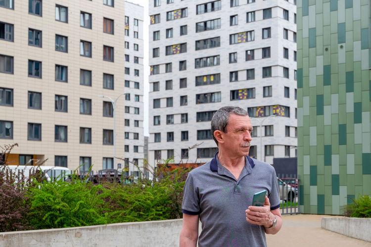Full length of man standing against buildings in city