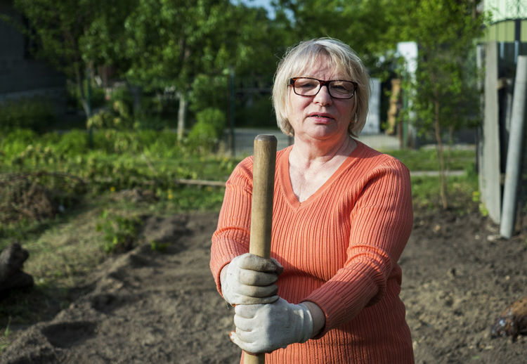 Caucasian middle-aged woman leans on the handle of the shovel in the garden Adult Adults Only Caucasian Day Eyeglasses  Garden Gardening Handle Human Body Part Human Hand Leans Middle-aged One Person One Senior Woman Only One Woman Only Only Women Outdoors People Portrait Senior Adult Senior Women Shovel Woman Women