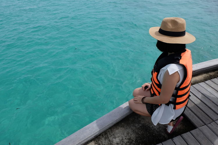 High angle view of woman wearing life jacket and hat while sitting on pier by sea