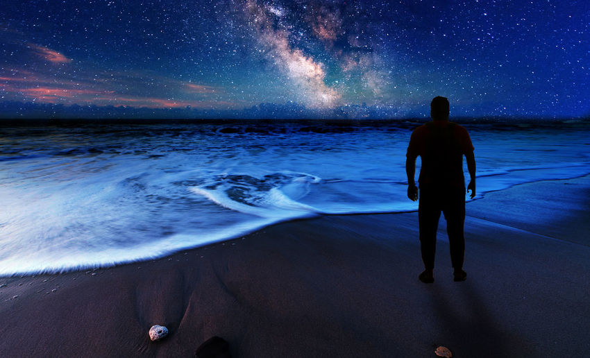 Rear view of man looking at sea during night