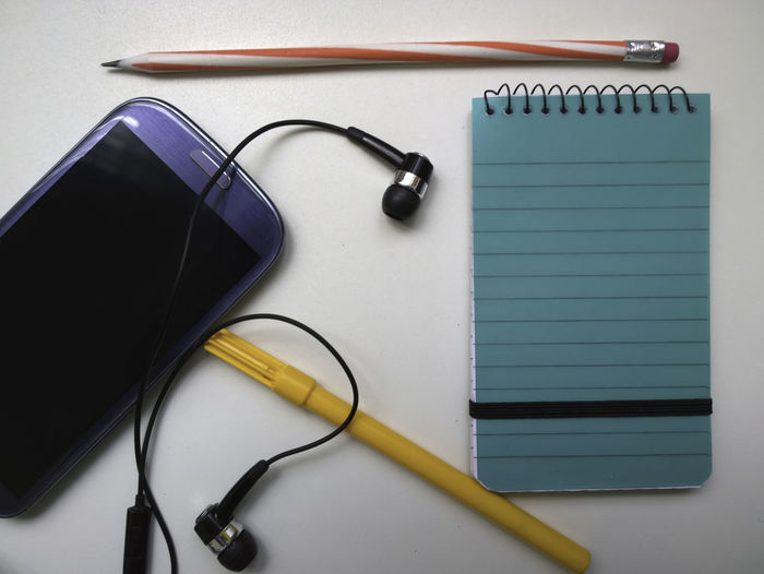 Close-Up Of Mobile Phone And Pens On White Background