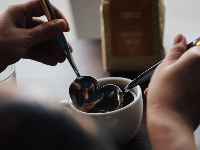 Cropped Image Of Hands Holding Spoons In Black Coffee At Cafe