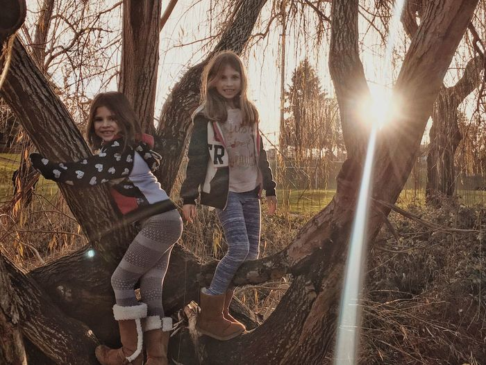 Portrait Of Happy Friends Standing On Tree At Park