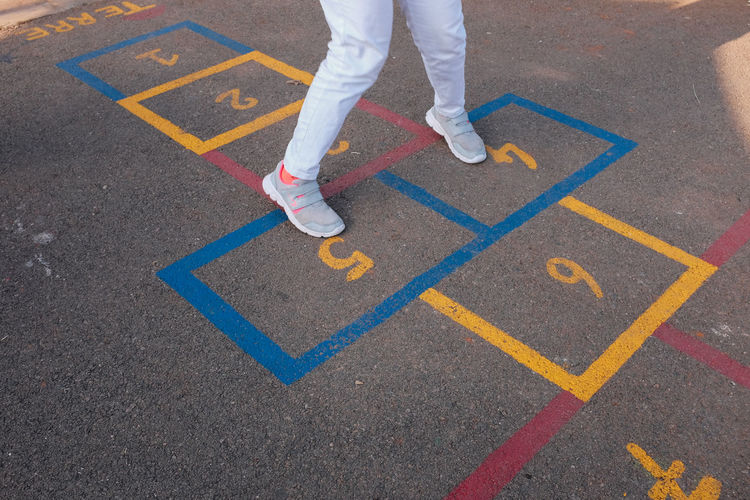 Low section of child playing hopscotch on road