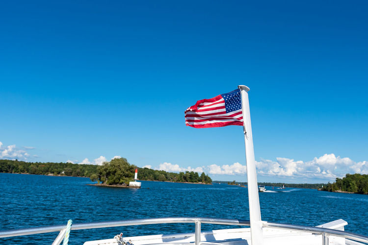 Thousand Island Lake US Flag USA Beauty In Nature Blue Boat Tour Copy Space Day Flag Independence National Icon Nature Nautical Vessel Navy No People Outdoors Patriotism Pride Red Sea Sky Sunlight Water Wind