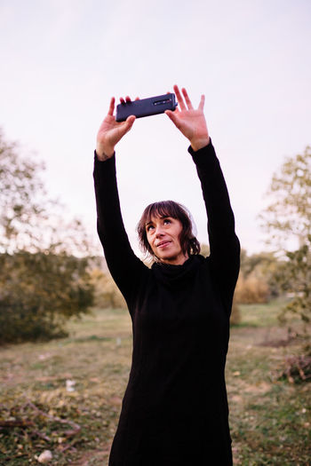 Woman doing selfie while standing at park