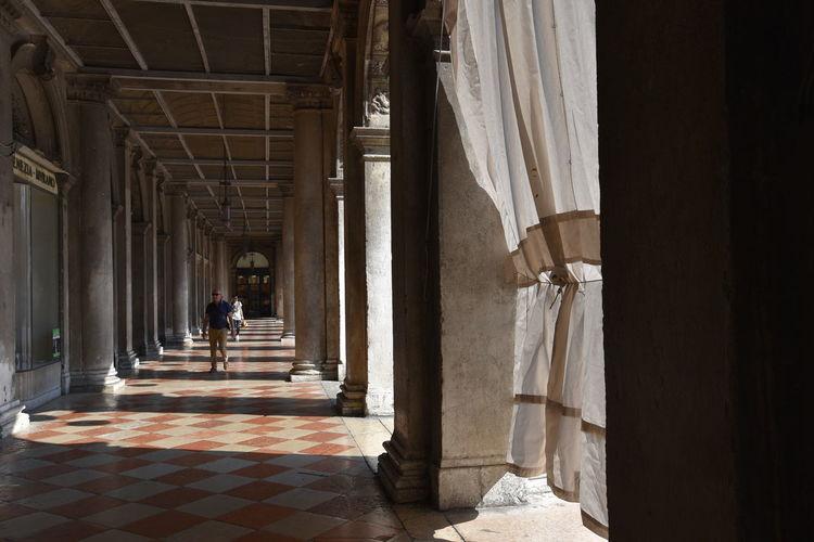 Rear view of people walking in corridor of building