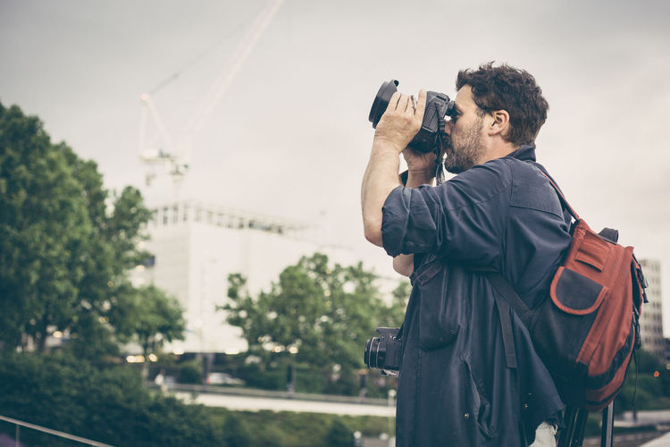 Man photographing with camera in city against sky
