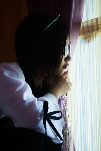 Close-up of girl looking through window