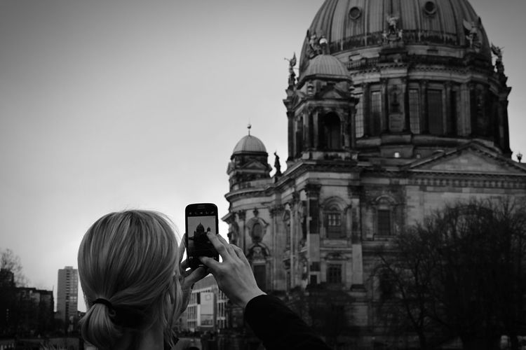 Rear View Of Woman Photographing Berlin Cathedral In Mobile Phone